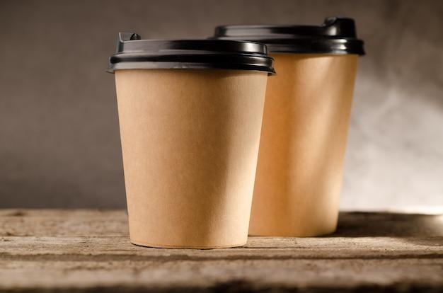 Taza de papel con café para ir contra la madera.