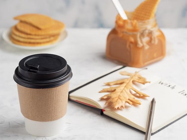 Taza de papel con café o bebida caliente sobre la mesa. bloc de notas con una hoja de deseos. de cerca