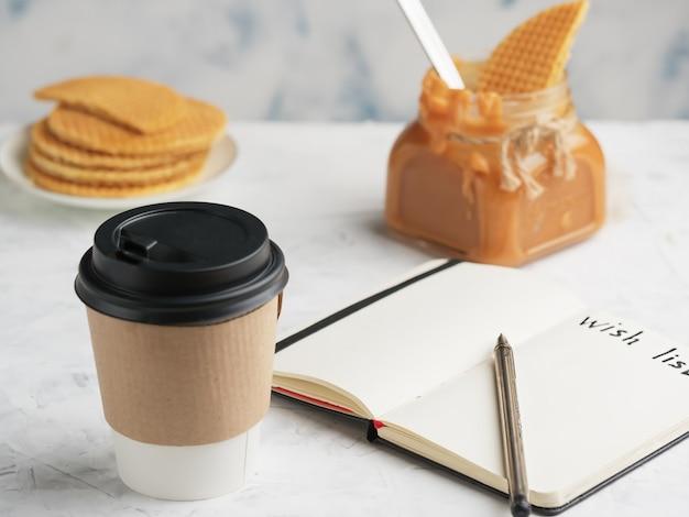 Taza de papel con café o bebida caliente sobre la mesa. bloc de notas con una hoja de deseos.