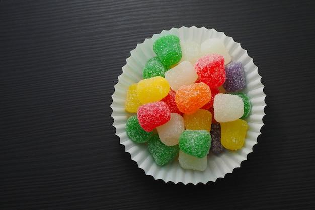 Taza de papel con mermelada multicolor sobre una mesa.