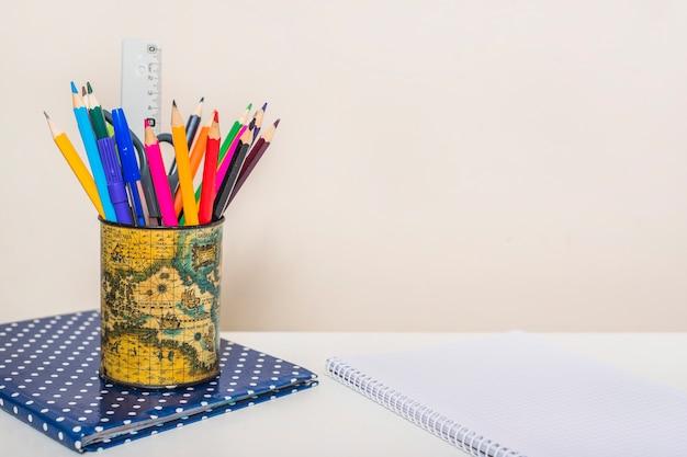 Taza con papelería en cuadernos