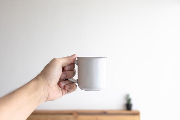 Taza pequeña blanca de café en una acogedora habitación blanca por la mañana.