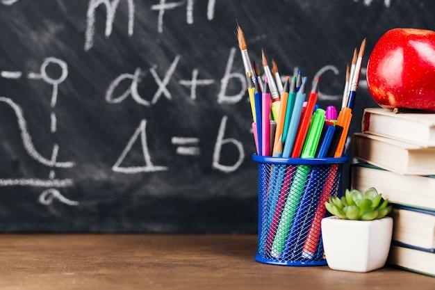Taza con pinceles brillantes y lápices en mesa