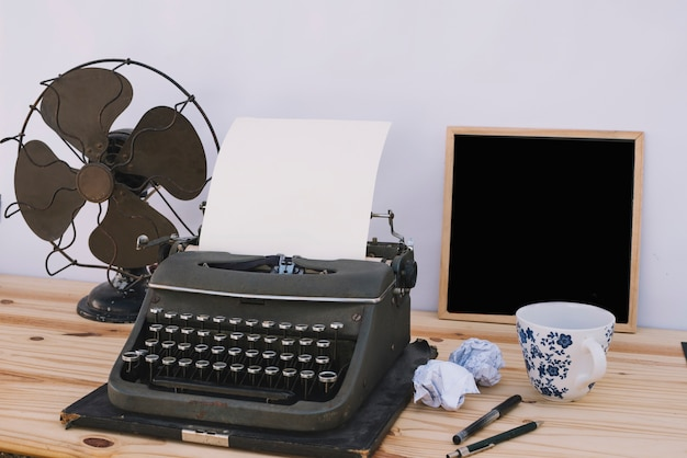 Taza y pizarra cerca de máquina de escribir y ventilador