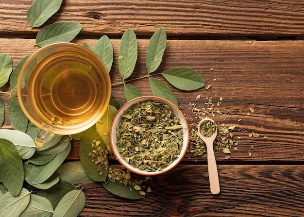 Taza plana de té y hojas de hierbas naturales