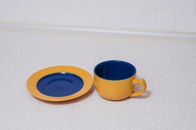 Taza y platillo azul amarillo sobre la mesa de la cocina.