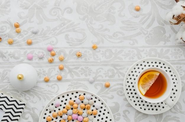 Taza y platillo de té de limón de jengibre con caramelos de colores sobre papel tapiz