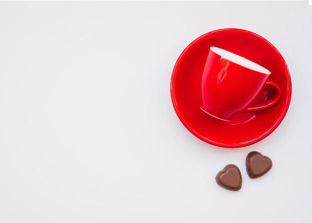 Taza en el plato cerca de dulces de chocolate dulces