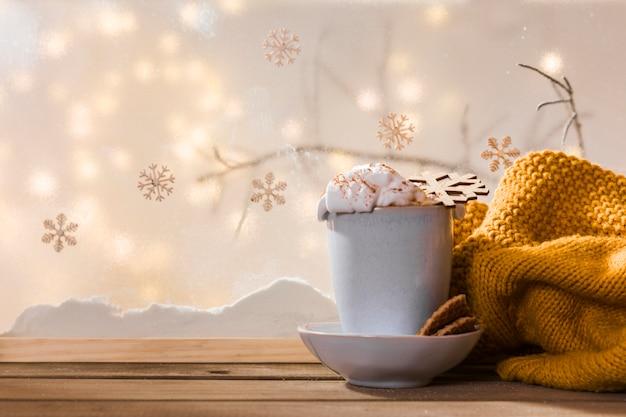 Taza en el plato con galletas cerca de la bufanda en la mesa de madera cerca del banco de nieve y luces de colores
