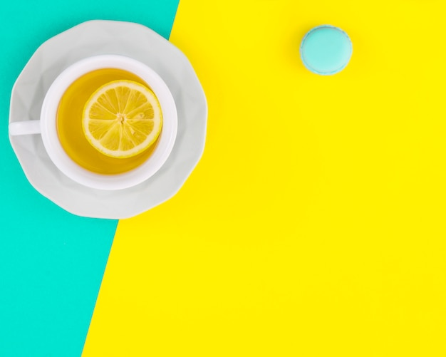 Taza y plato de té de limón blanco con macarrones sobre fondo turquesa y amarillo