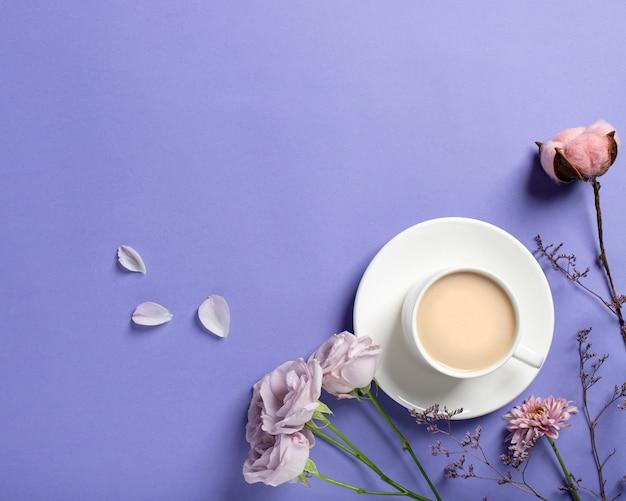 Taza de porcelana con café y hermosas rosas lilas, ramas de flores secas sobre un fondo lila. concepto de café de primavera. estilo plano, vista superior, lugar para texto