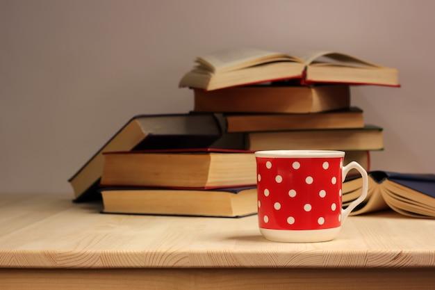 Taza de porcelana roja con lunares blancos y una pila de libros sobre una mesa de madera.