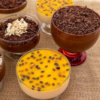 Taza de postre con mousse de chocolate con leche y virutas de chocolate blanco, mousse de ganache y mousse de maracuyá.
