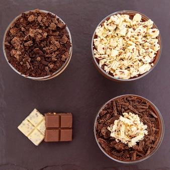 Taza de postre con mousse de chocolate con leche y virutas de chocolate blanco y mousse de ganache.