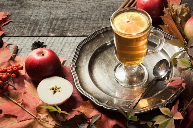 Taza que se calienta de té con la decoración de las hojas y de las calabazas de otoño en el tablero de madera. caen bodegones