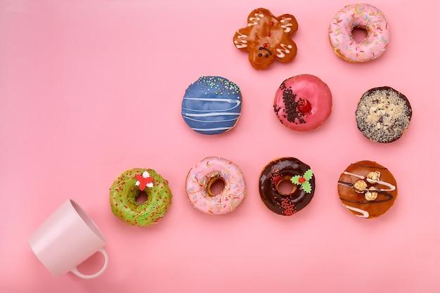 Una taza de la que vuelan las rosquillas dulces, sobre un fondo rosa