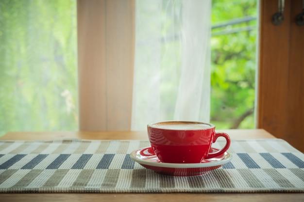 Taza roja, café con leche en forma de corazón sobre mantel de madera
