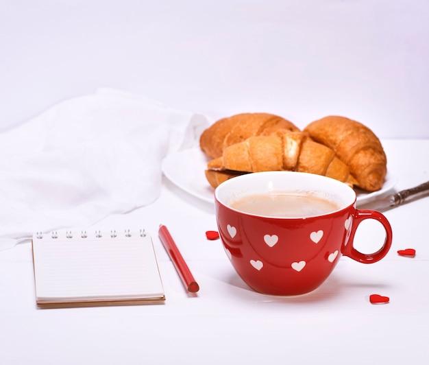 Taza roja con café negro y un cuaderno de papel.
