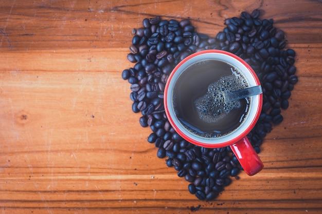 Taza roja de café negro con los granos de café en estilo del color de la visión superior y del vintage.