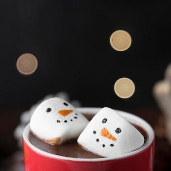 Taza roja de chocolate caliente con primer plano de malvaviscos