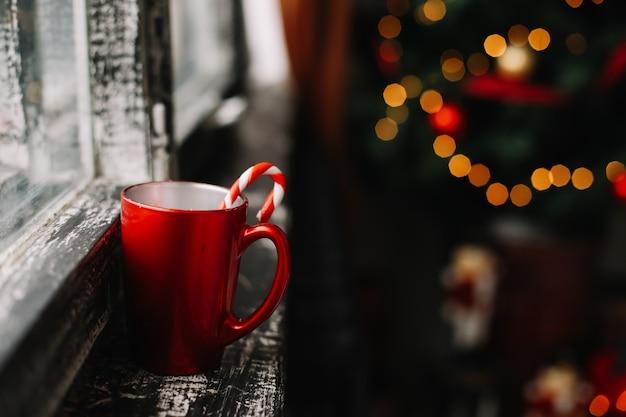 Taza roja y dulces con un árbol de navidad decorado en el fondo
