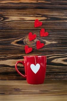 Taza roja con etiqueta de bolsa de té en forma de corazón