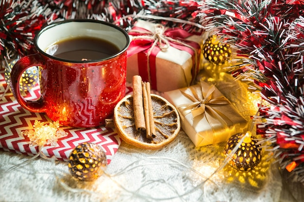 Taza roja con té y adornos navideños