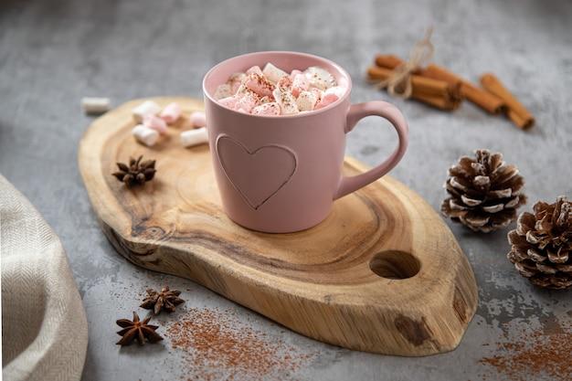 Taza rosa con cacao aromatizado y malvaviscos blanco-rosa, ramas de canela y anís estrellado sobre una tabla de madera