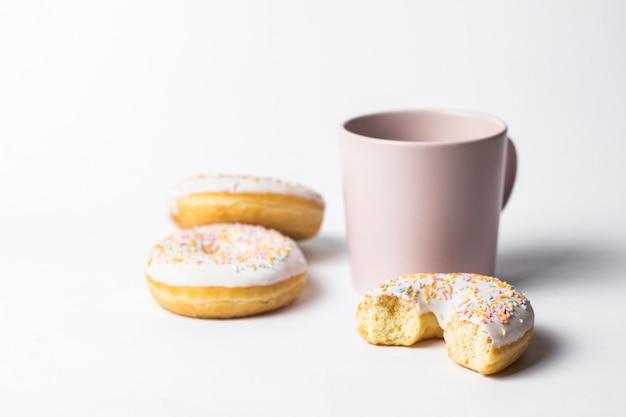 Taza rosa con café o té y donuts sabrosos frescos, dulce dulce decorativo multicolor sobre un fondo blanco. concepto de panadería, pasteles frescos, delicioso desayuno, comida rápida.