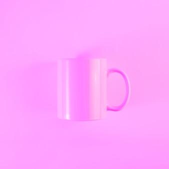 Taza rosa pintada con asa contra fondo coloreado.