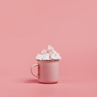 Taza rosa sobre una superficie rosa llena de malvaviscos en forma de corazones.