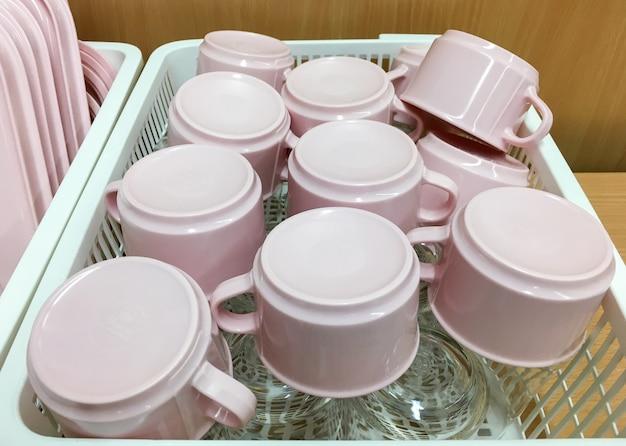 La taza rosa y el vaso se guardan en la cesta de plástico.