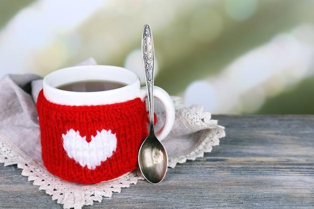 Taza de sabroso té caliente, sobre mesa de madera, sobre fondo claro