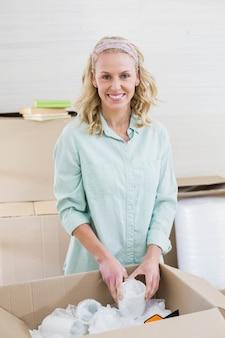 Taza sonriente del embalaje de la mujer en una caja