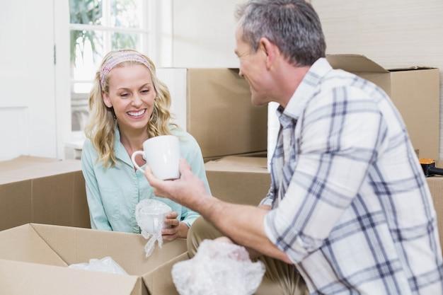 Taza sonriente del embalaje de los pares en una caja en casa