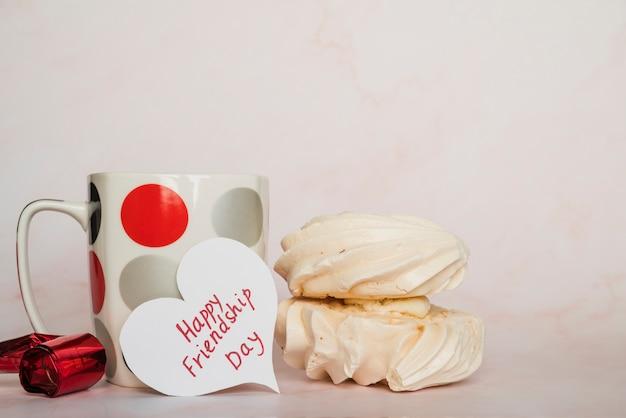 Taza y tarjeta de san valentín con inscripción y dulces.