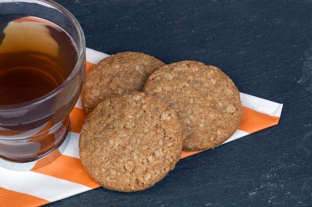 Taza de té acompañado de galletas de avena sobre una servilleta estampada sobre fondo oscuro
