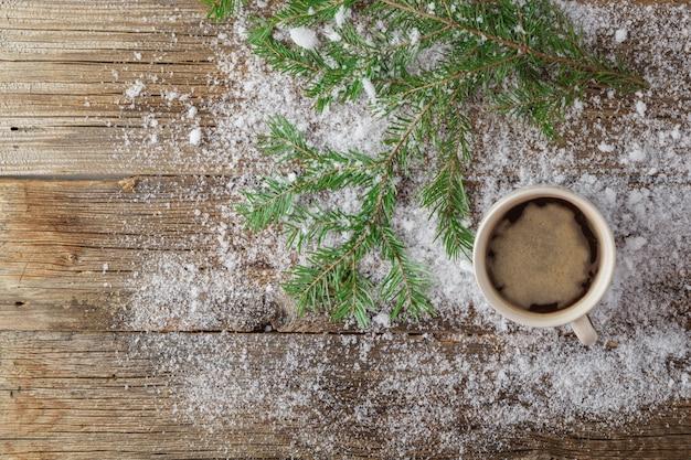 Taza de té y árbol de navidad verde sobre la nieve en la mesa de madera