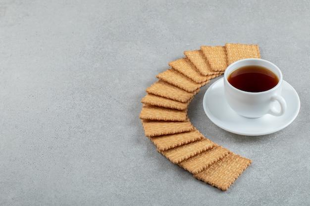 Una taza de té aromático con galletas saladas sobre un fondo gris.