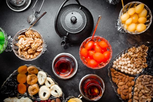 Taza de té aromático y jarrones con mermelada, frutas secas