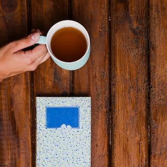 Taza de té aromático y libro sobre madera vieja