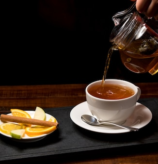 Taza de té aromático y tazón con limón