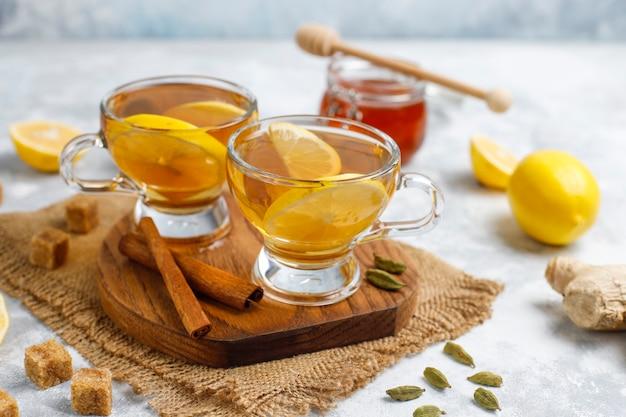Una taza de té, azúcar morena, miel y limón sobre hormigón. vista superior, espacio de copia