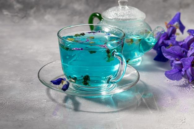 Una taza de té azul caliente con flores de guisante. guisantes azules para una bebida saludable, desintoxica el cuerpo. mesa gris