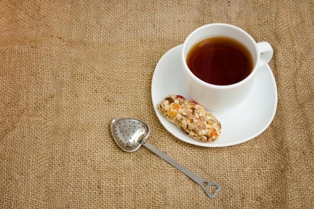 Taza de té, barra de muesli y colador de té sobre tela de saco. vista superior