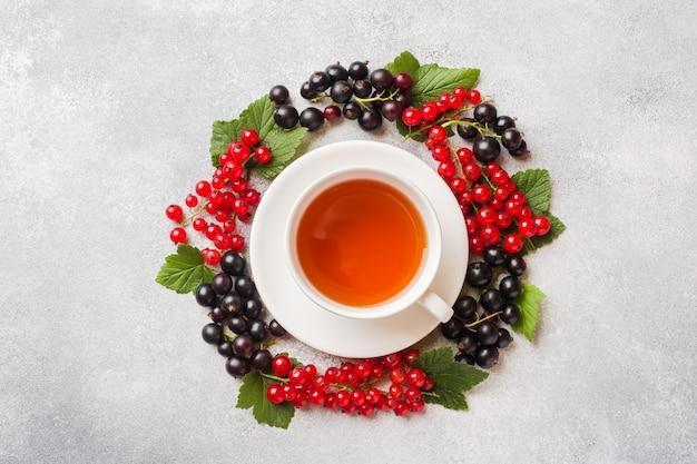 Taza de té y bayas frescas de la grosella negra y roja en la tabla gris. copia espacio