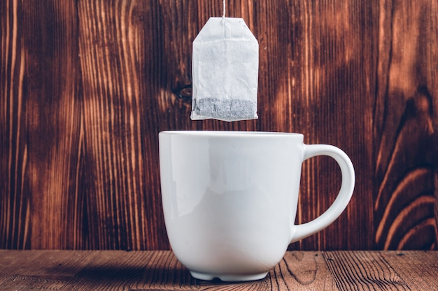 Una taza de té blanco con una bolsita de té