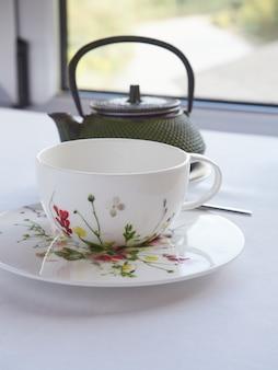 Taza de té blanco decorado con flores pintadas y tetera oriental delante de una ventana blanca