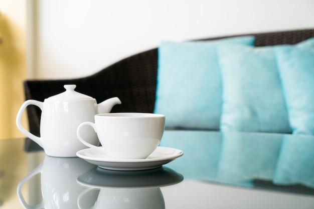 Taza de té blanco con tetera en la mesa en la terraza