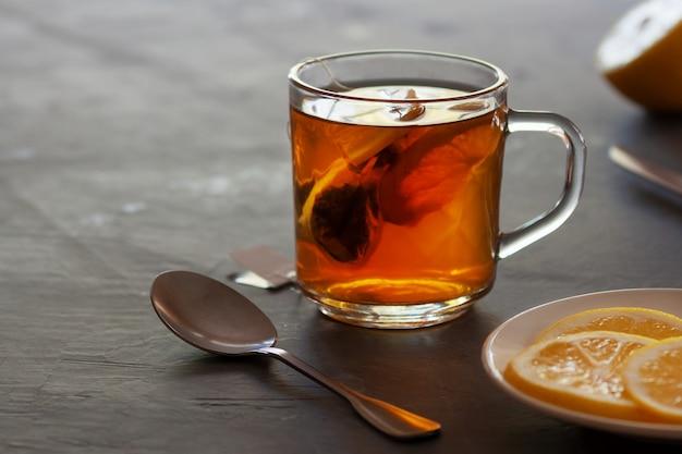 Taza de té con una bolsita de té y rodajas de limón